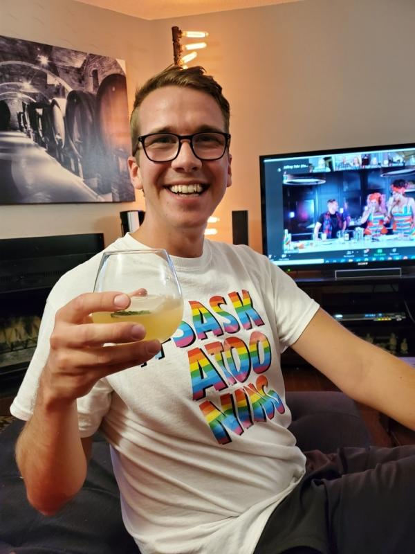 A man has a drink in front of a TV
