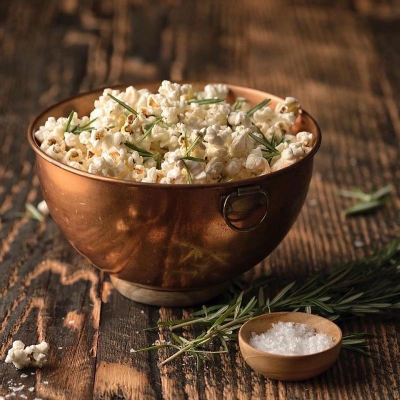 A copper bowl filled with Popcorn sitting on a rustic wooden table at Micro Bar + Bites