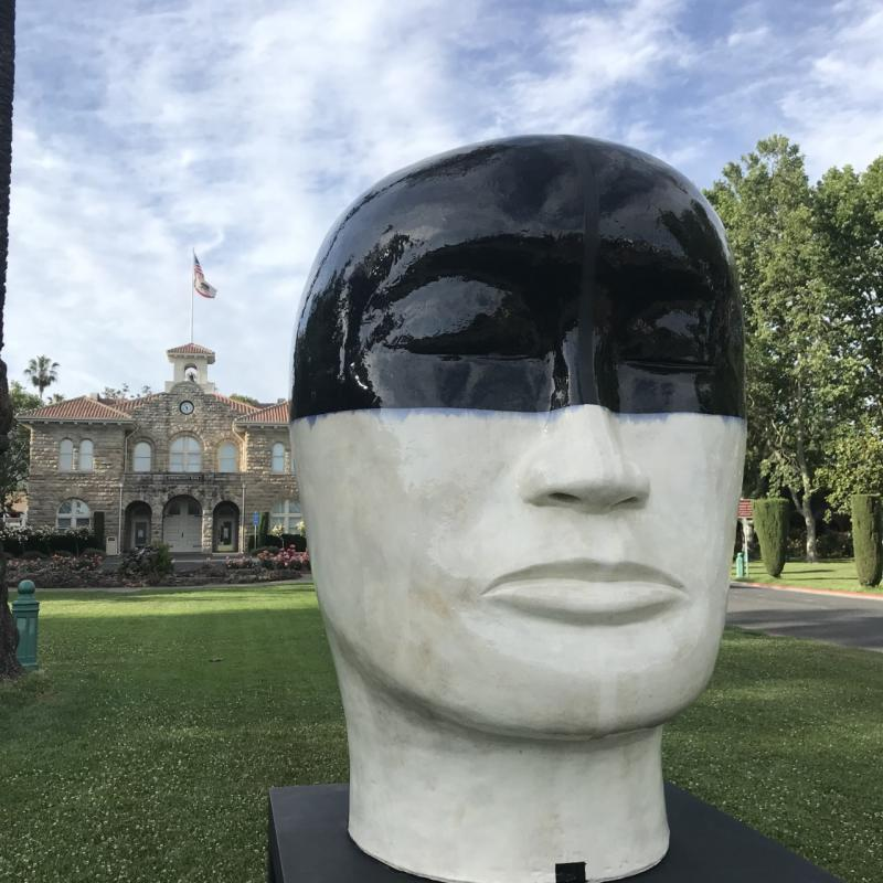 A large head sculpture in front of the Sonoma City Hall building in Sonoma, California with a blue sky background