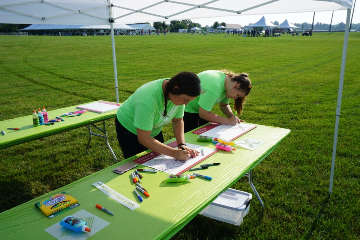 Two girls make signs for Pelotonia