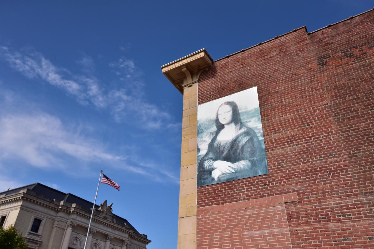 Mona Lisa painting on side of brick building in downtown Eau Claire