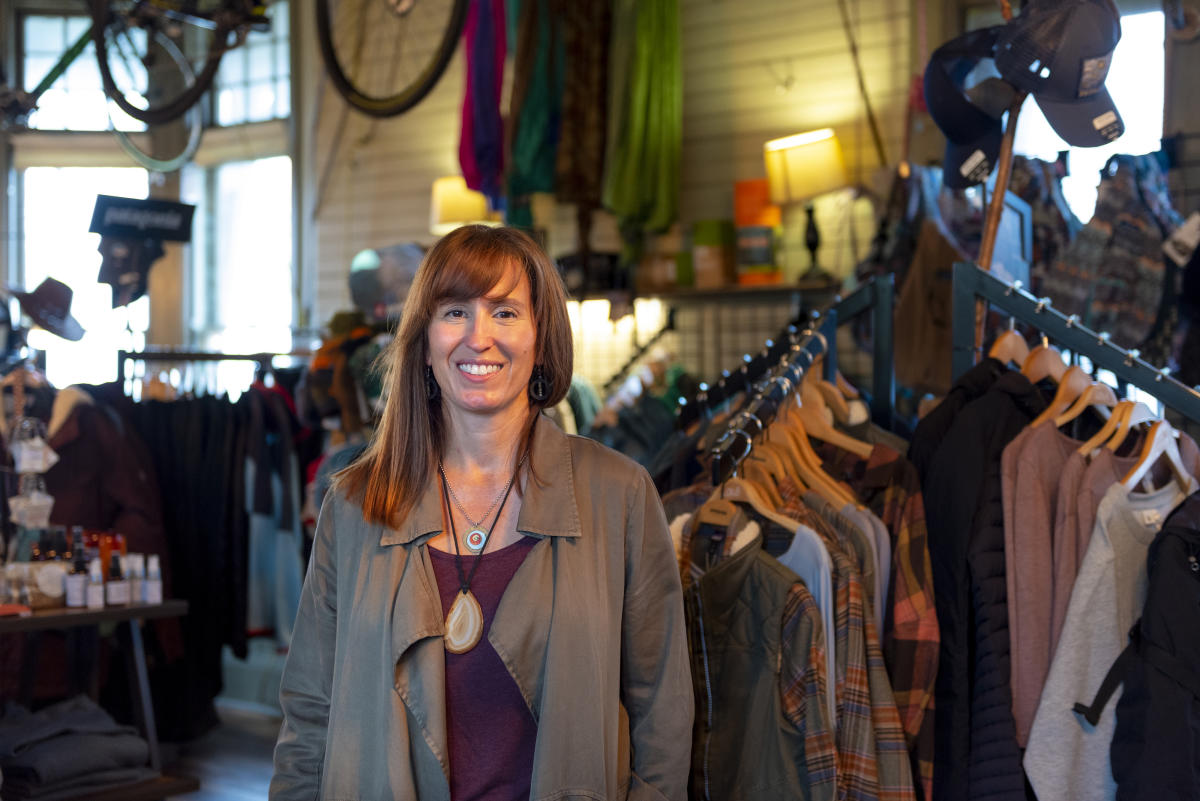 Cara Hall of Fort Wayne Outfitters in Fort Wayne, Indiana standing in her shop with outdoor recreation apparel and gear in the background.