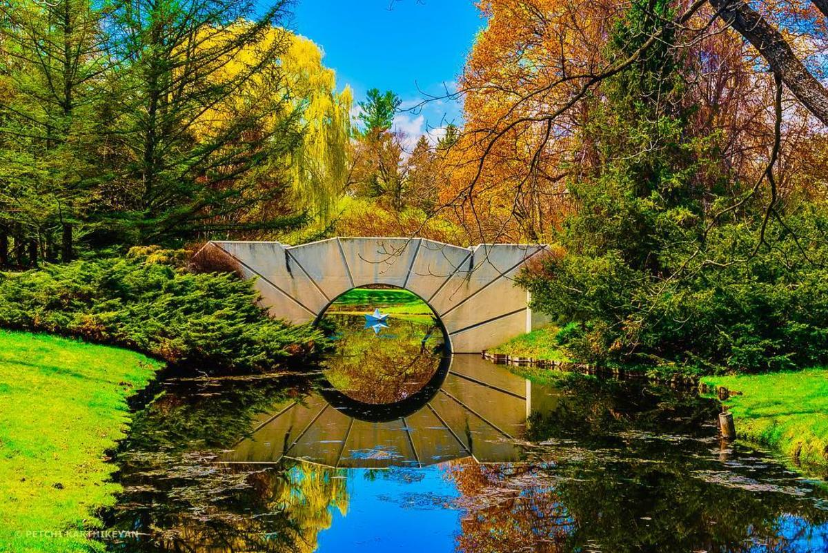 The sun bridge at Dow Gardens in Midland reflecting onto the water, framed by colorful trees