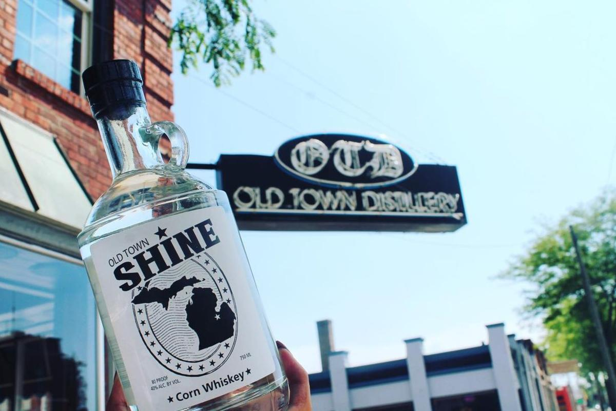 Bottle of OTD's Old Town Shine held up in front of the Old Town Distillery sign in Old Town Saginaw