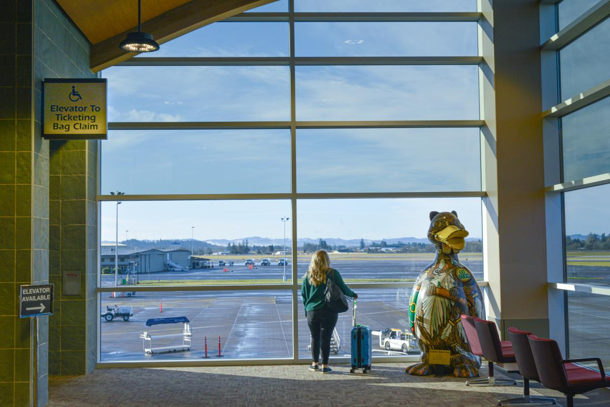 A woman with a rolling carry on suitcase stands in front of large windows at the airport looking out over the tarmac.