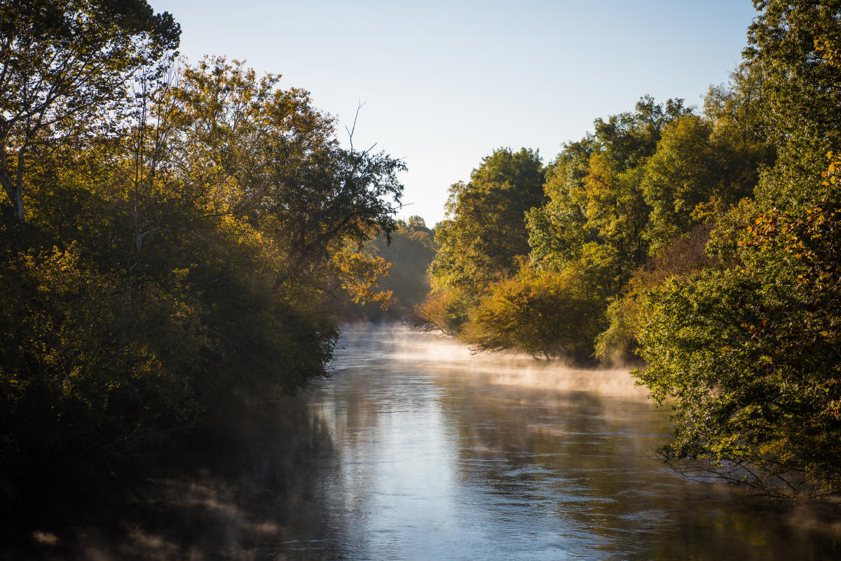 steamy river on fall morning with sunlight and colors