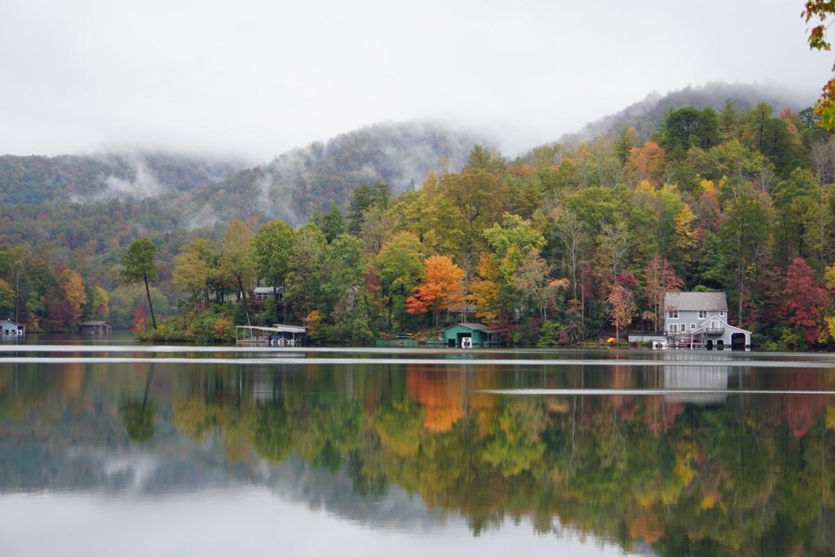 Mist drifts into the autumn foliage along the shore of Lake Lure.