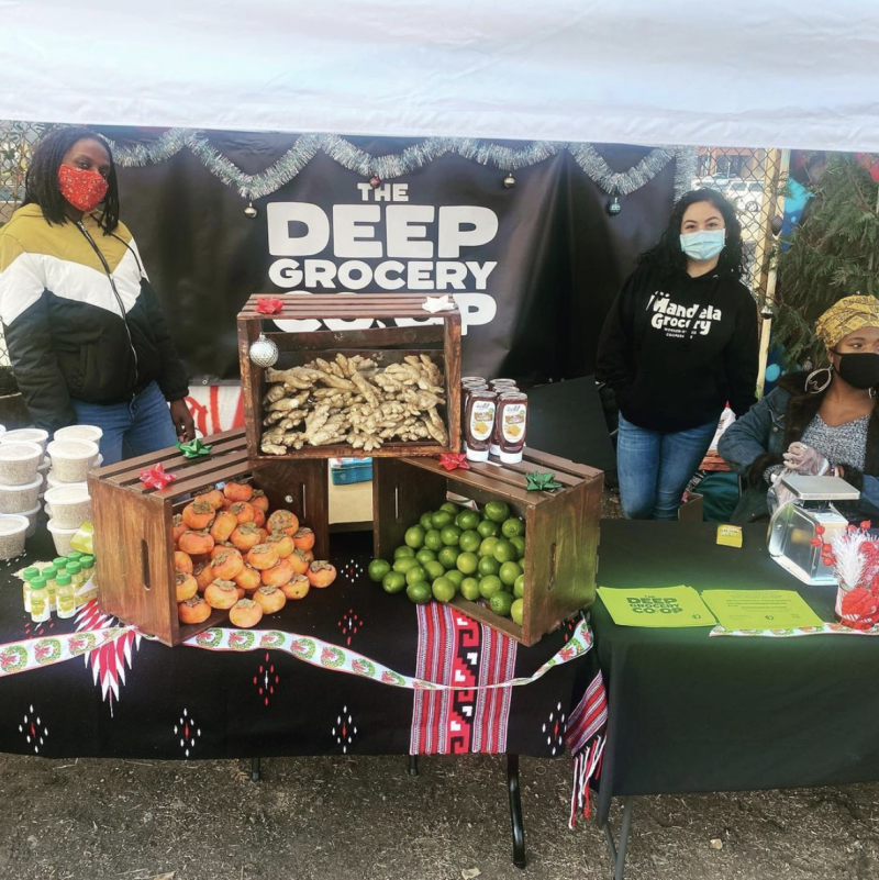 Woman working at the DEEP Grocery COOP stand with produce on display