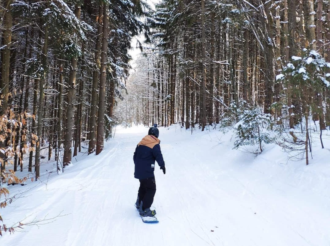 Man snowboarding down wooded trail