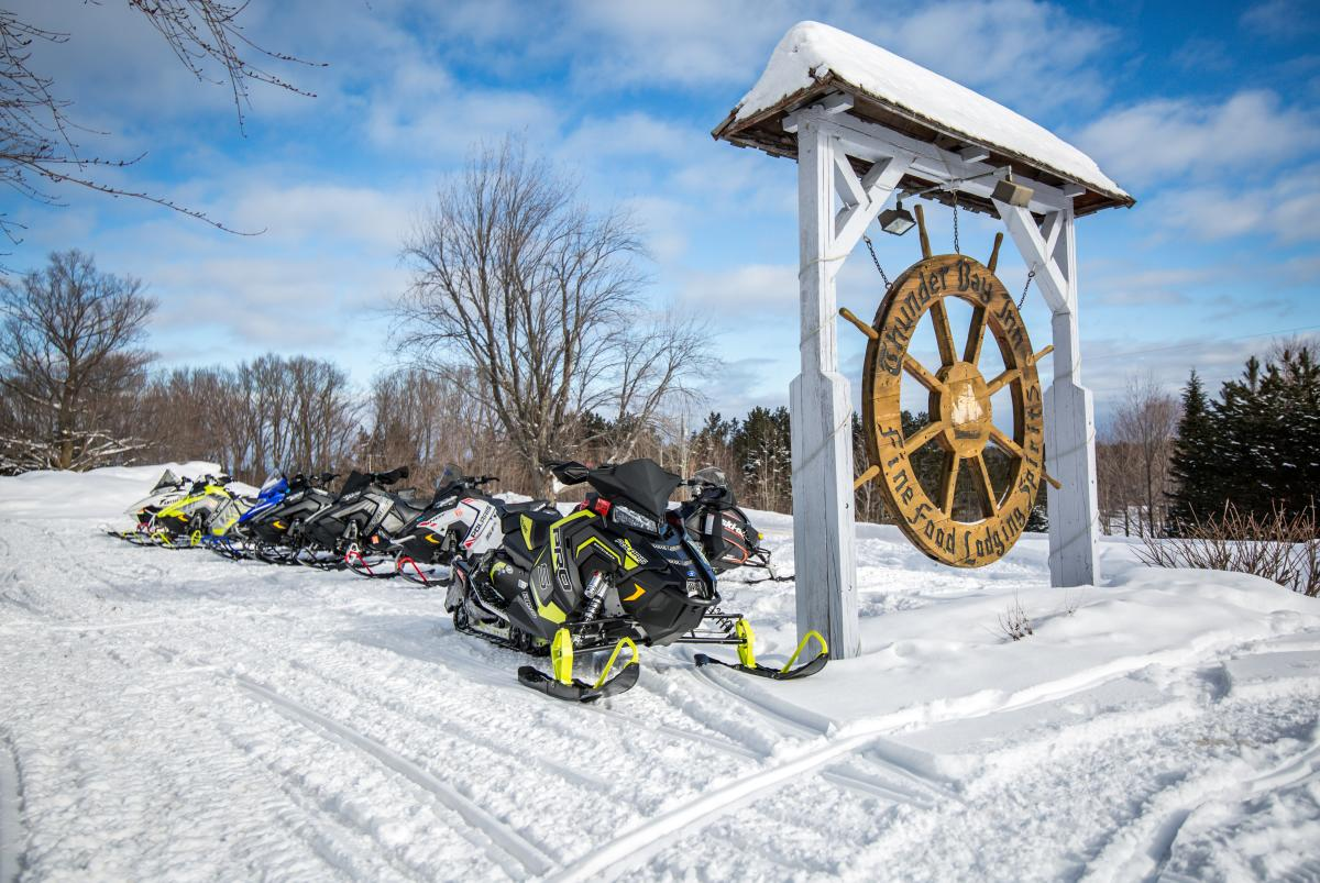 Snowmobiles lined up by Thunder Bay Inn's entrance sign.