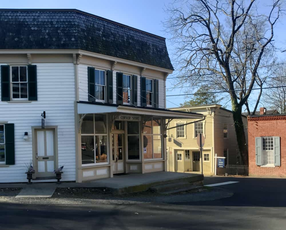 View of the Corner Store in Waterford, VA with its white siding, black tile roof and large front porch