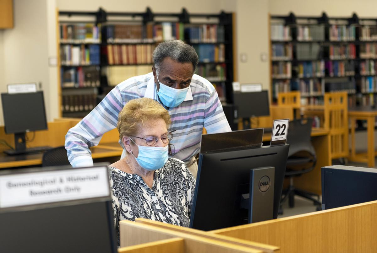 Two adults wearing a mask researching in the Genealogy Center in Fort Wayne, Indiana