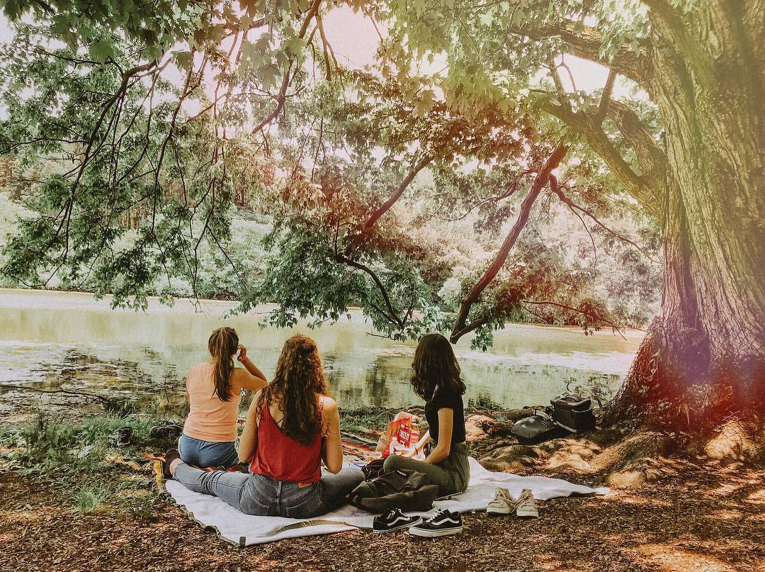 Girls sitting on the bank of water enjoying a picnic at the Morton Arboretum