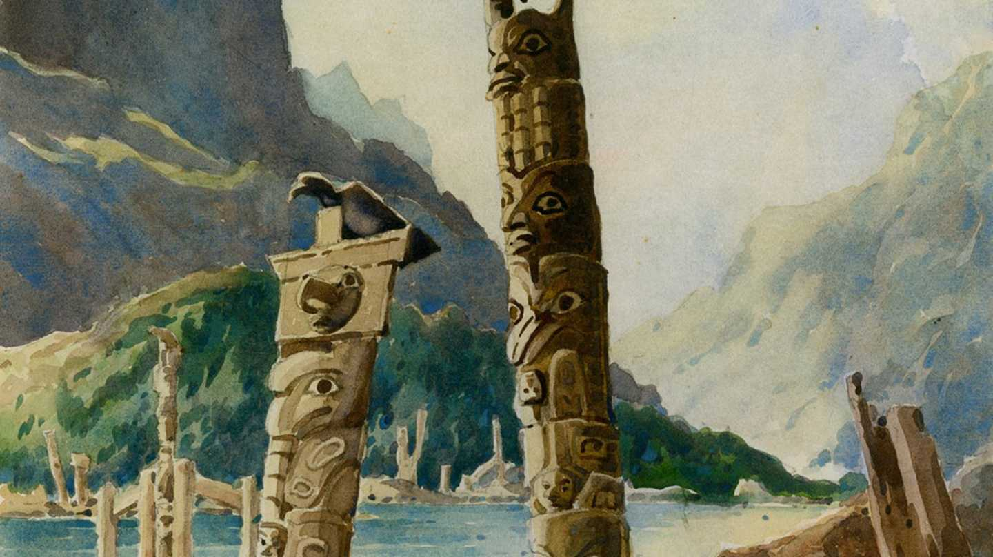 Totem poles by water and mountains