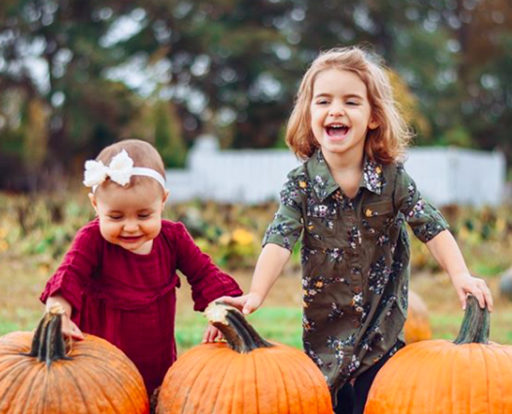 Two young girls with pumpkins at oasis family farm