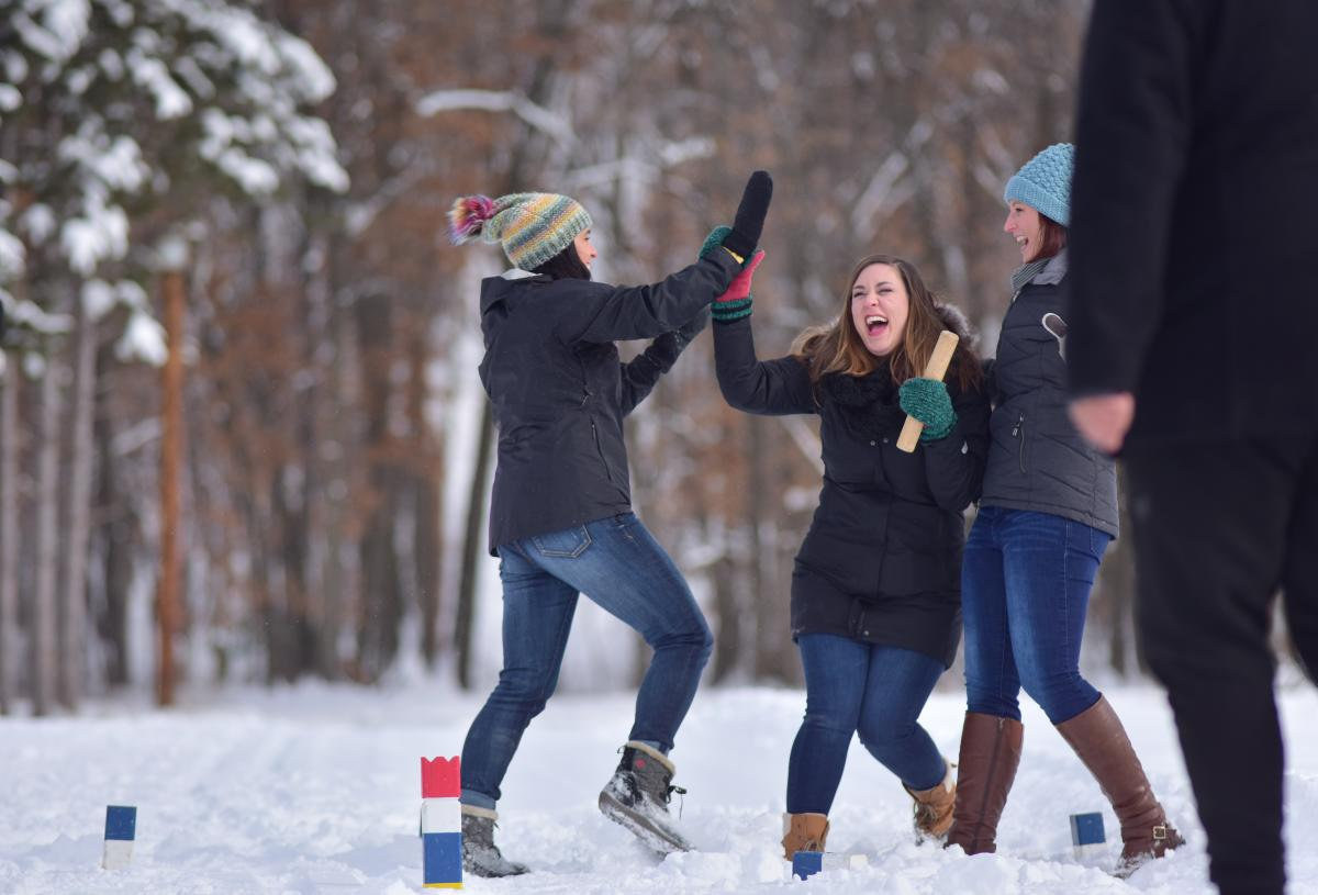 Woman cheering each other during a Winter Kubb game at Pinehurst Park
