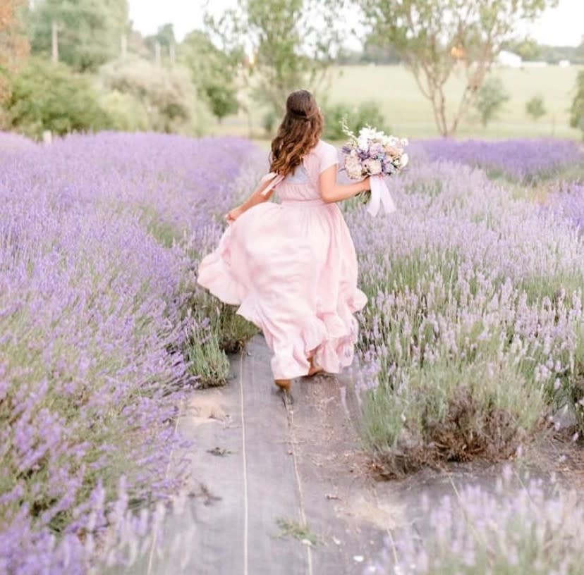 Woman running through lavender at Black & Blue Berry Farm