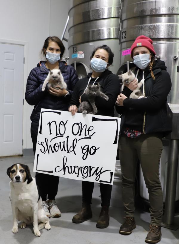 """Chehalem staff and pets hold Giving Season sign that reads """"no one should go hungry"""""""