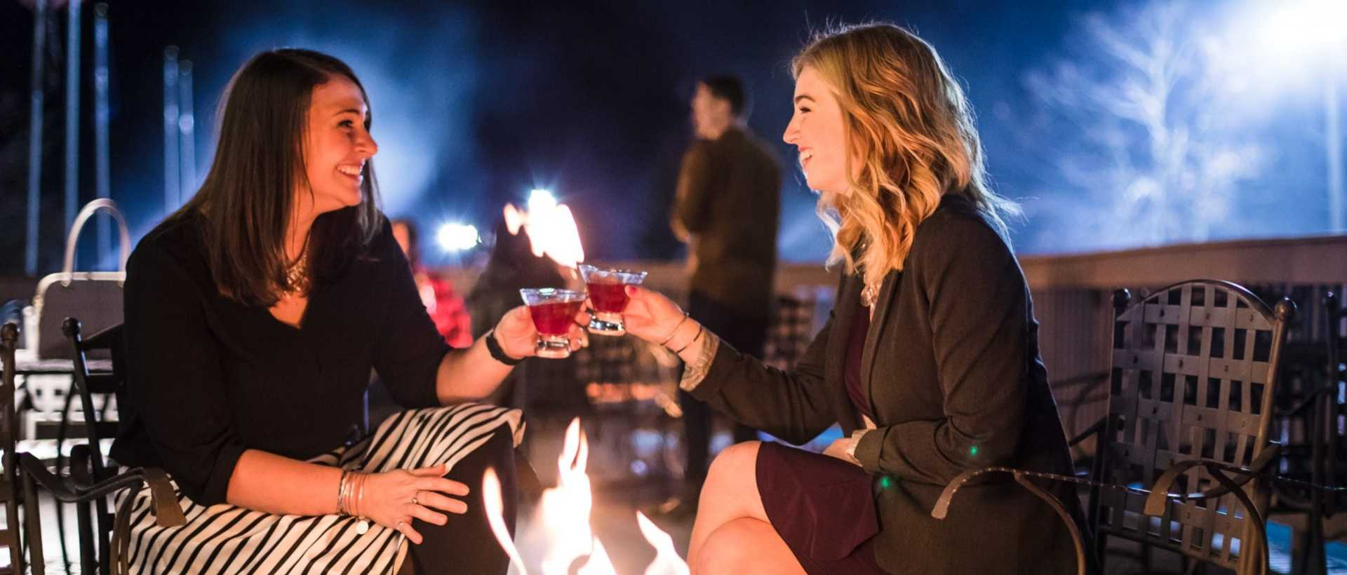 Two women enjoying drinks outdoors near a fire pit at Montage Mountain in Scranton, Lackawanna County, PA.