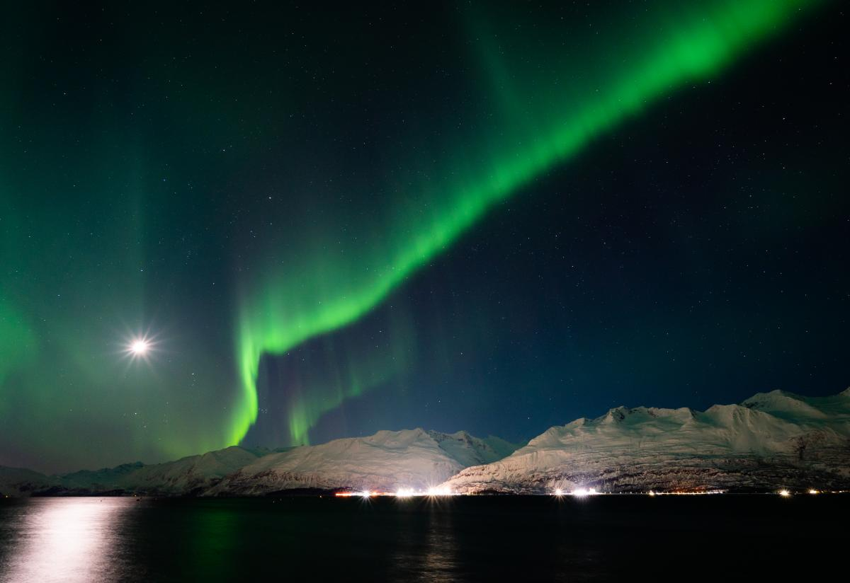 Aurora over a seaside town, port, and mountains