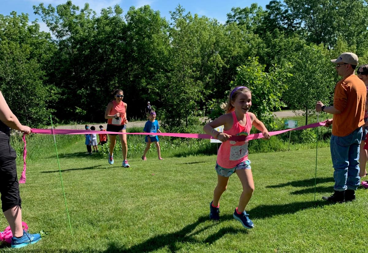 A young girl cheers as she crosses the 5K finish line in the park.