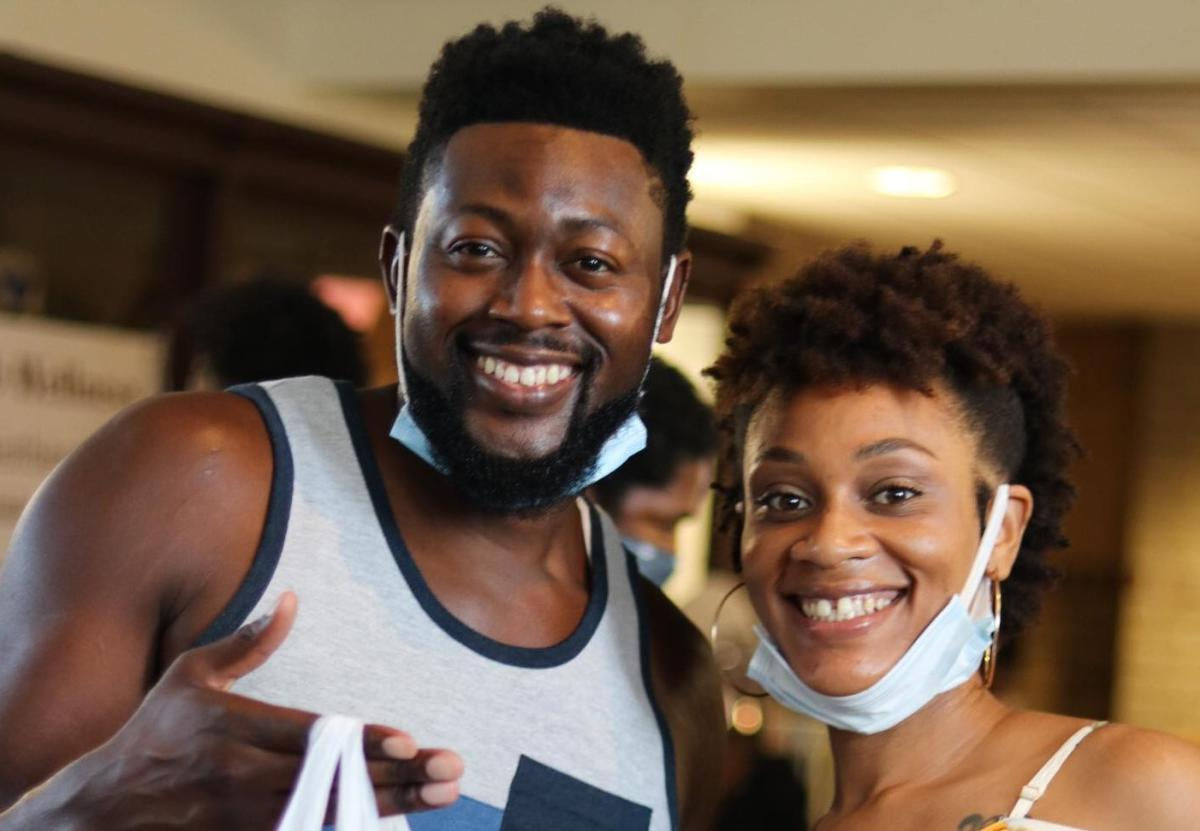 An African-American man and woman smiling at the camera. Their face covers are down around their chins.