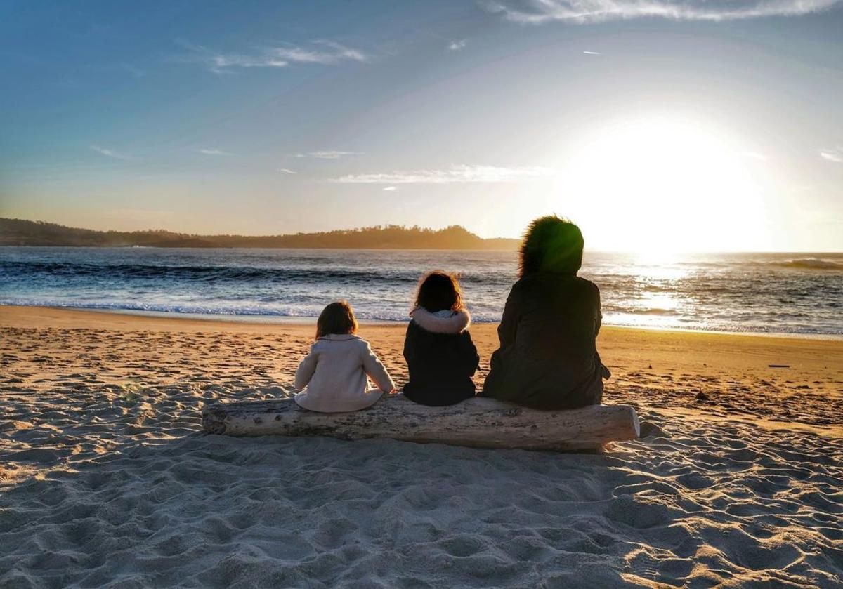 Mother and her two daughters sitting on a log facing the beach while the sun sets.