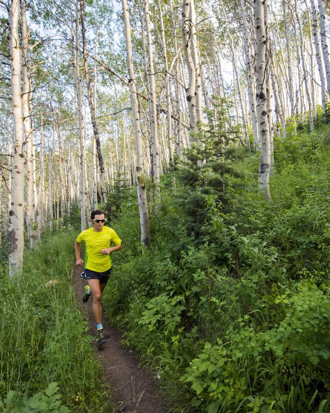 Man in yellow shirt running on trail through aspen treets