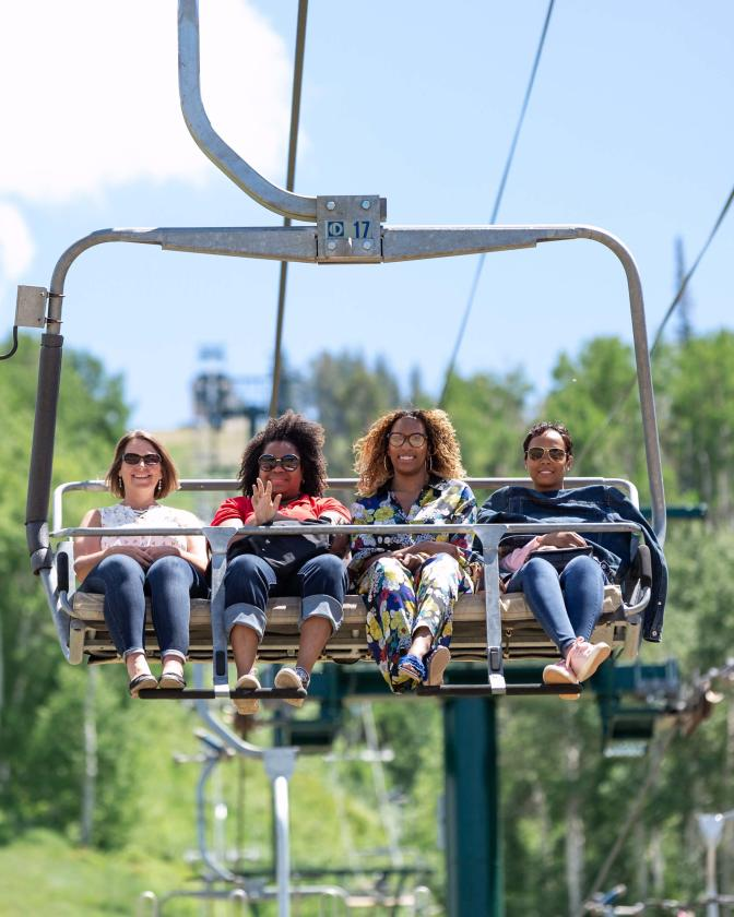 Four women riding on chairlift at Deer Valley Resort