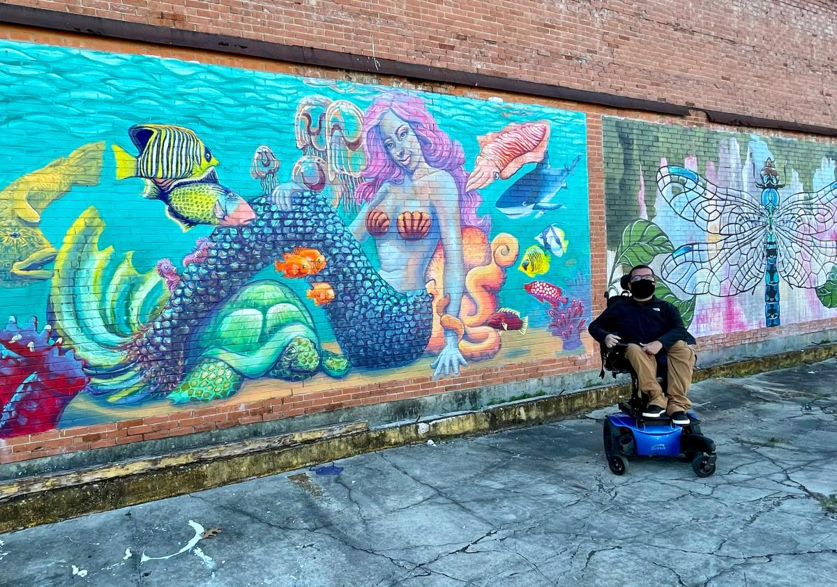 cory in front of mural of mermaid and sea animals