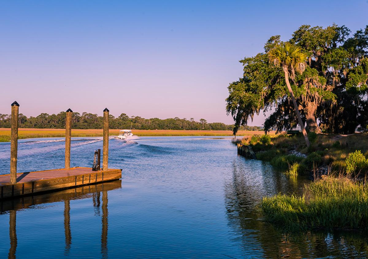 A boat cuts through the waters near a dock at Little St. Simons Island.