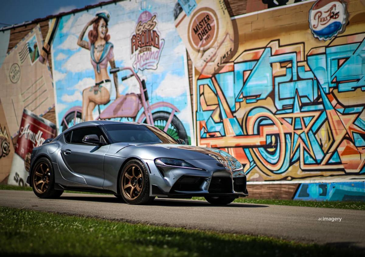 Sports car parked in front of a mural