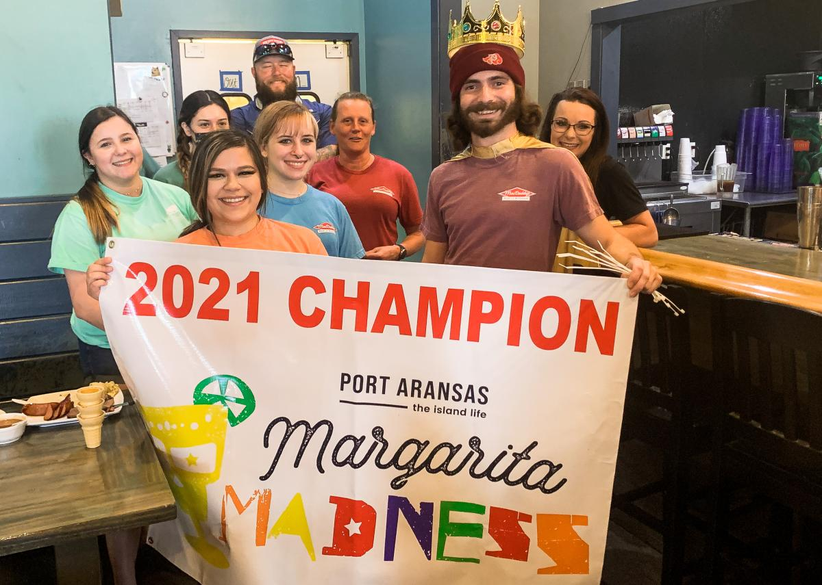 """A group of people hold up a banner that says """"2021 Champion Margarita Madness"""""""