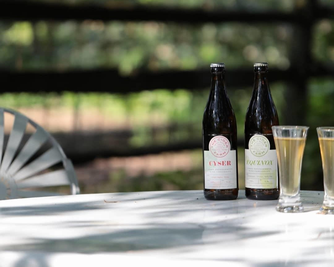 A bottle of Cider Farm Equinox and Cider Farm Cyser sitting with two filled glasses on a white table outside.