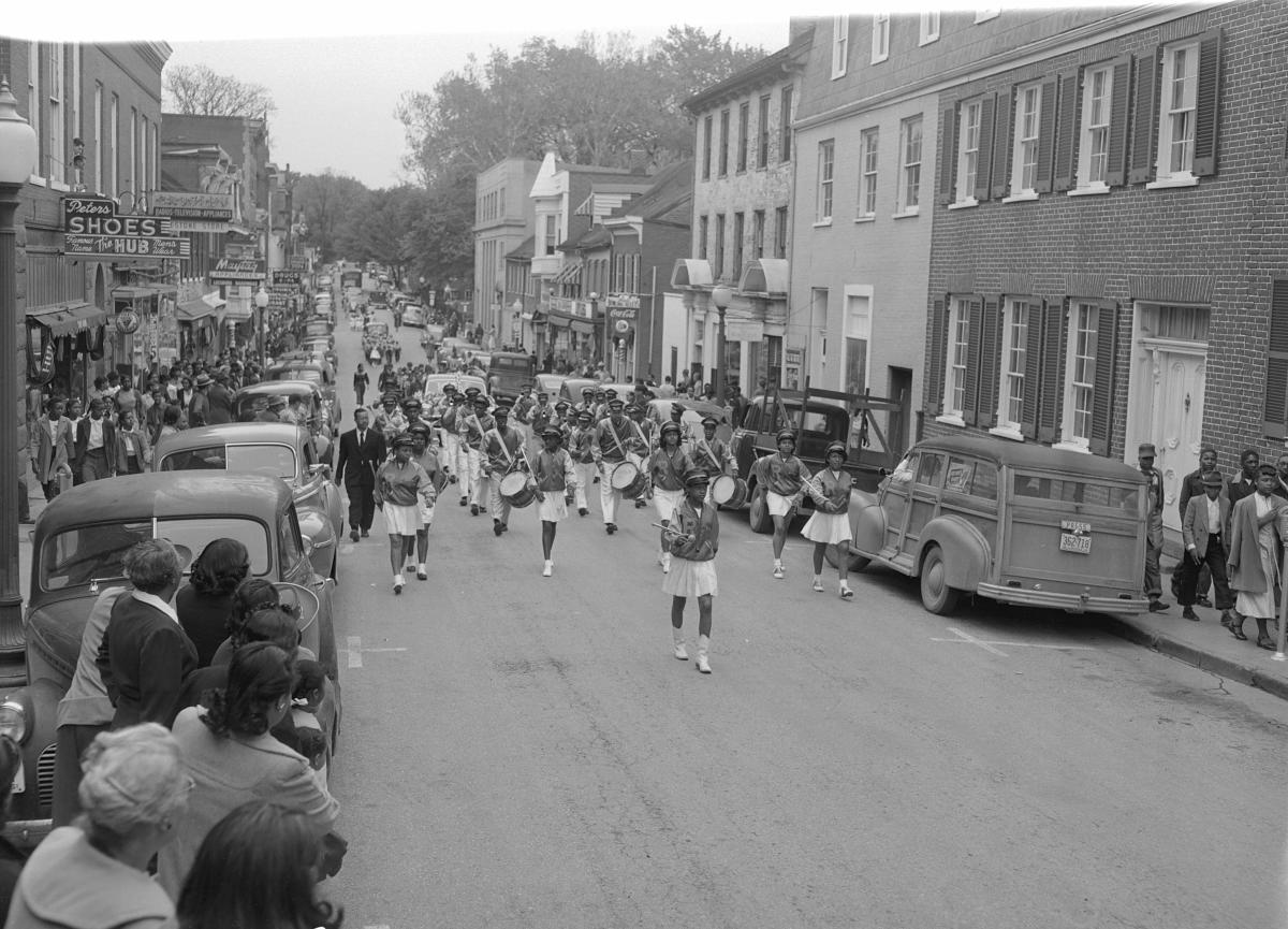 African Americans line the streets of Douglas, VA to watch their youth marching band and cheerleaders in the downtown parade.