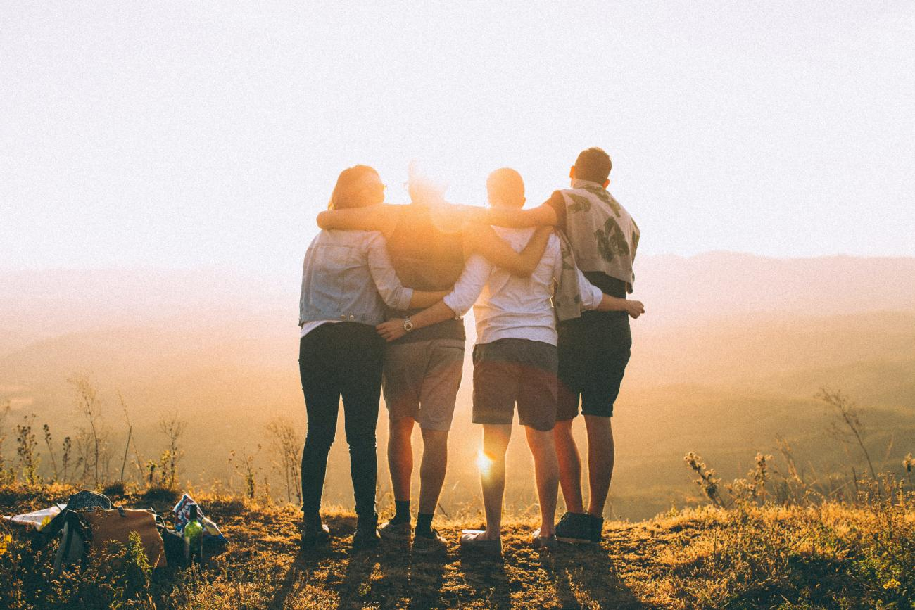 Group-friends-hugging-after-hiking-a-hill