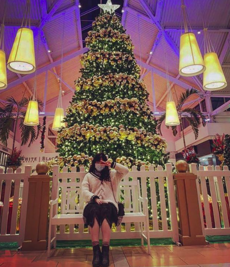 A woman posing in front of the big christmas tree at marketfair