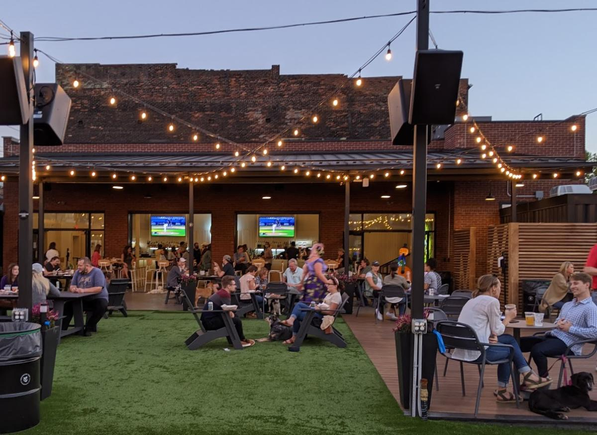 Strings of white lights hanging over Covington Yard, filled with seated people and a dog.