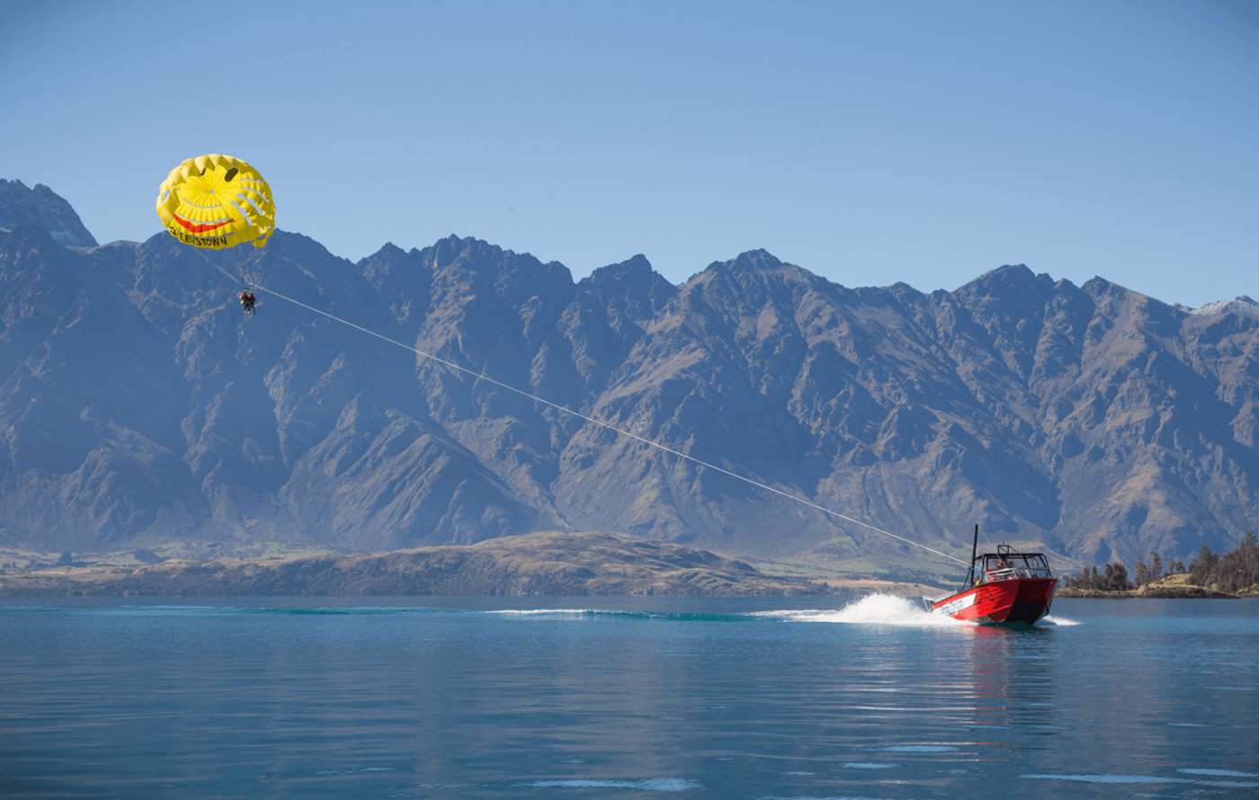 Boat towing a parasail in front of the remarkables