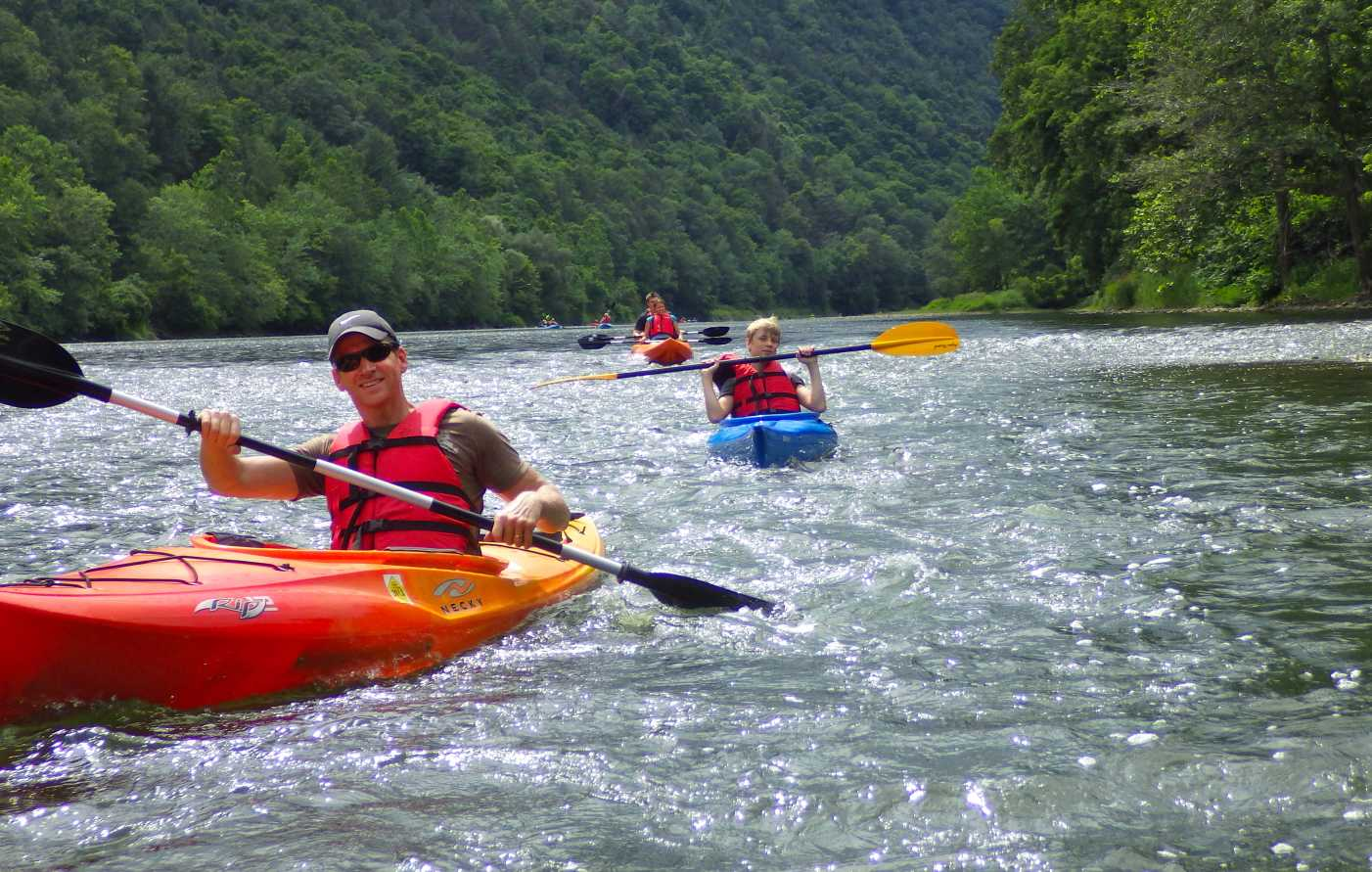 people kayaking down a river