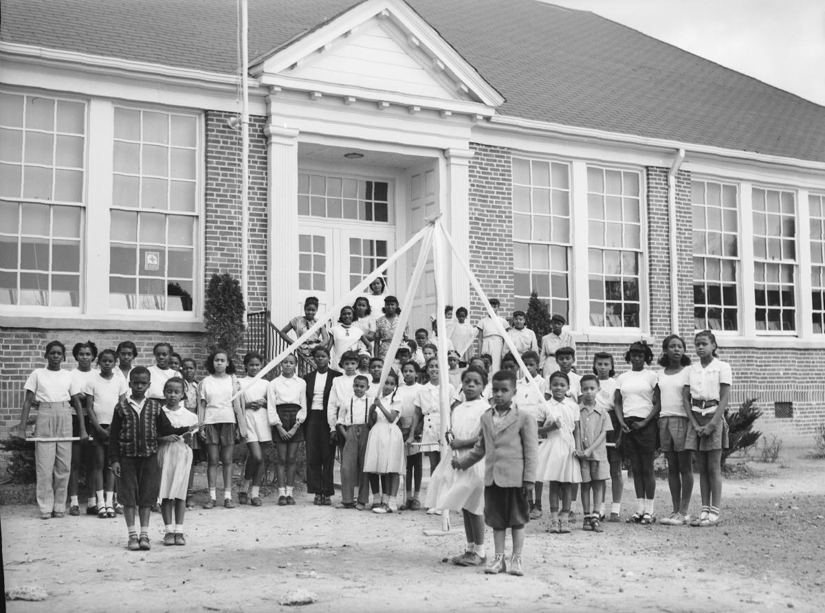 Black children stand outside their schoolhouse to celebrate May Day at George Washington Carver School.