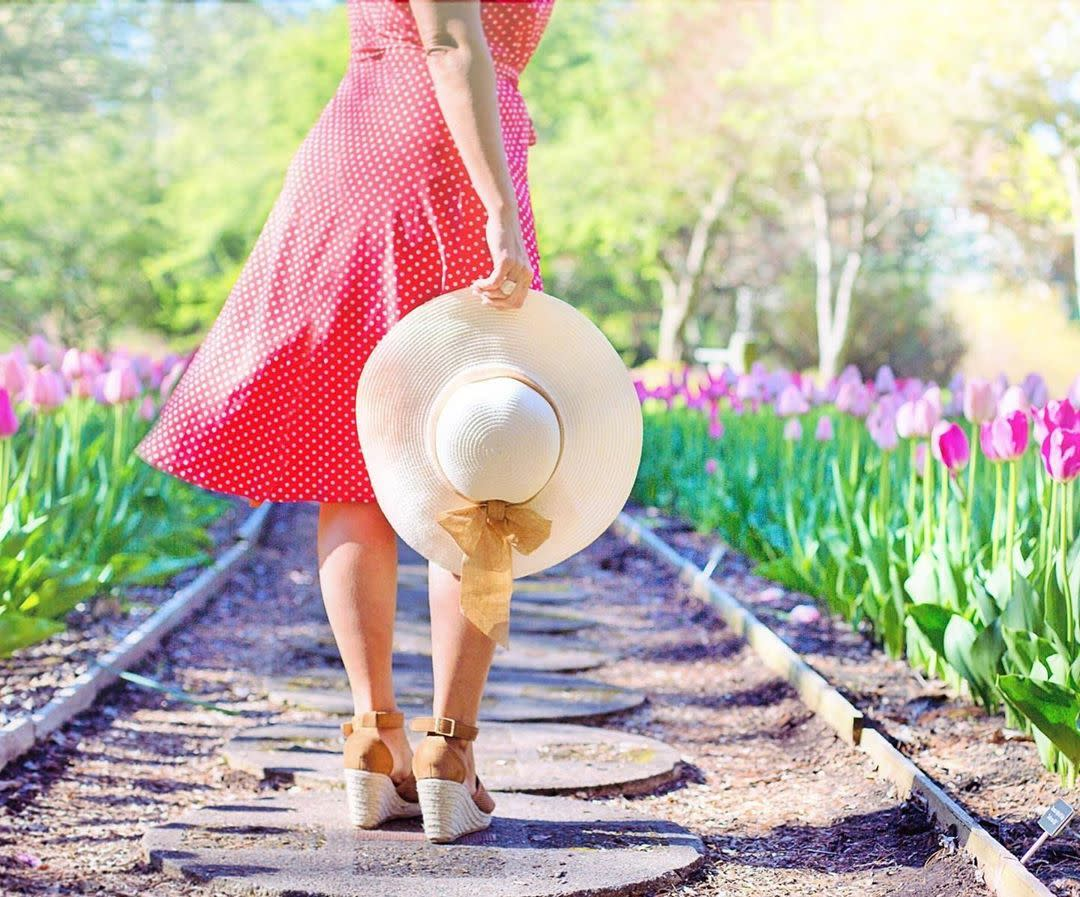 Woman in a sundress holding a sun hat while walking a tulip-lined path in bloom at Dow Gardens in Midland