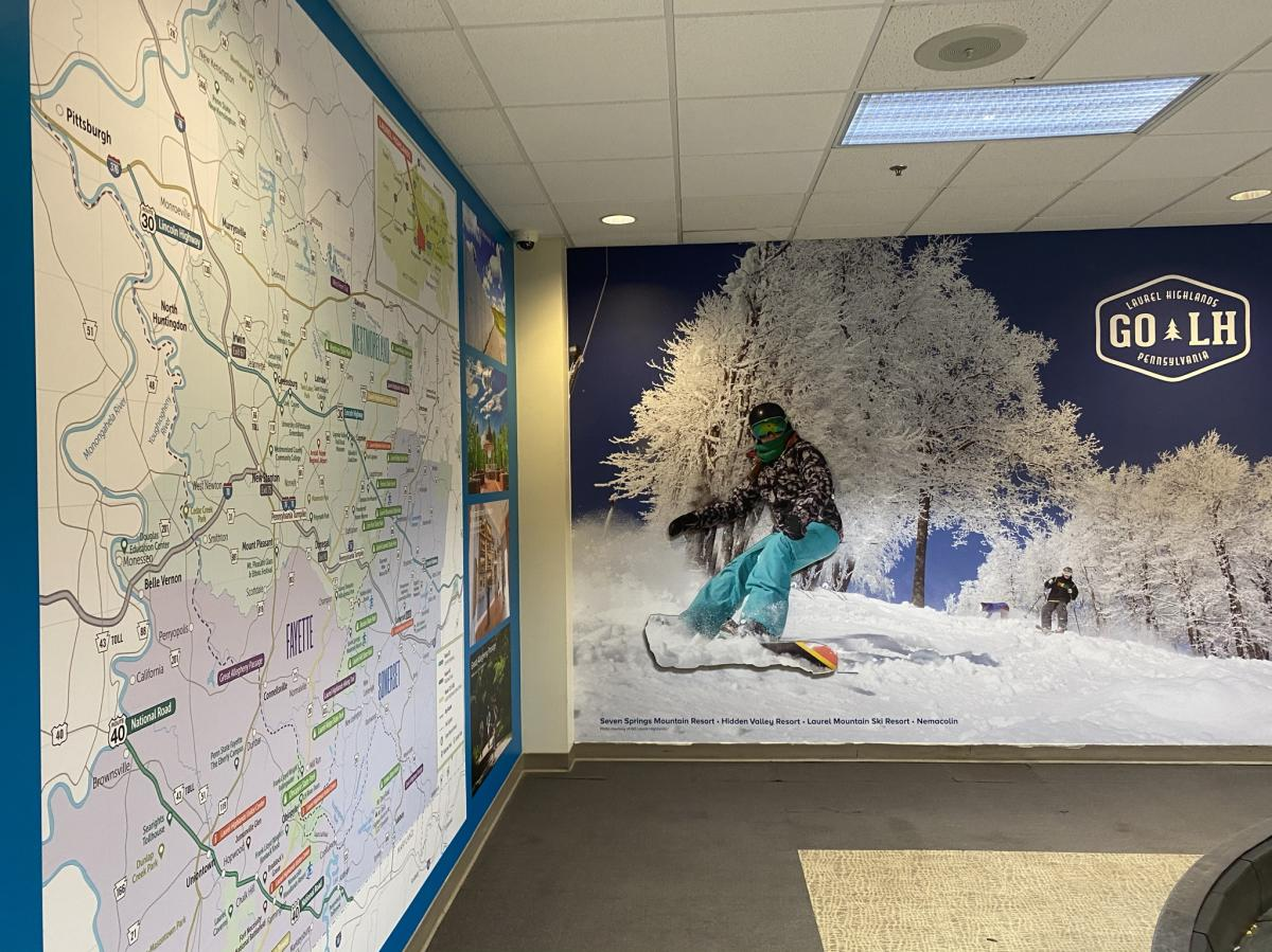 Regional map and three-dimensional skier welcome passengers at Arnold Palmer Regional Airport