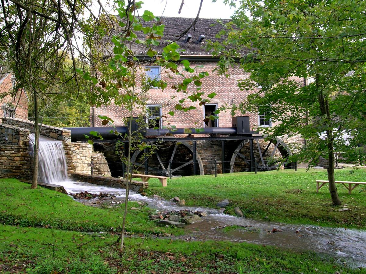 Historic Aldie Mill on a sunny day with a heavy stream of water