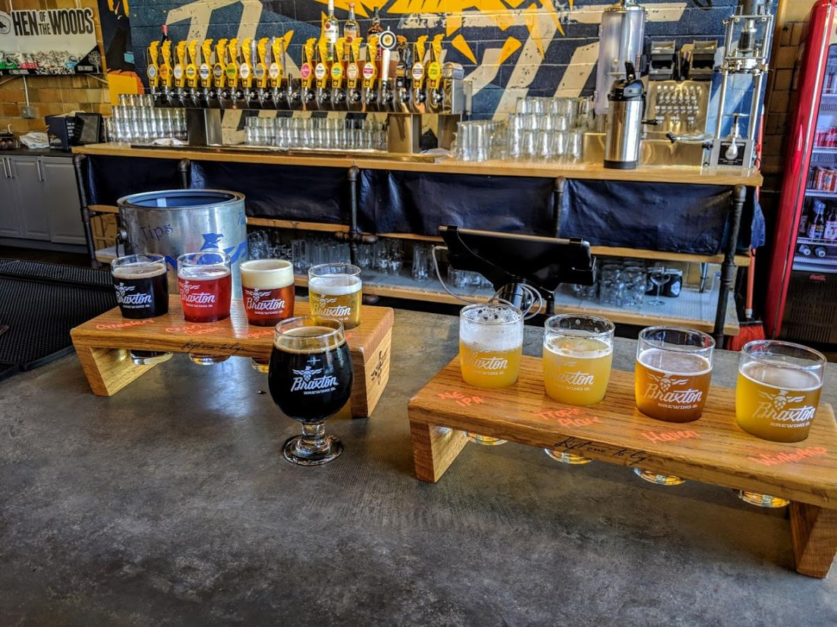 two beer flights on the bar at Braxton Brewery with the taps in the background