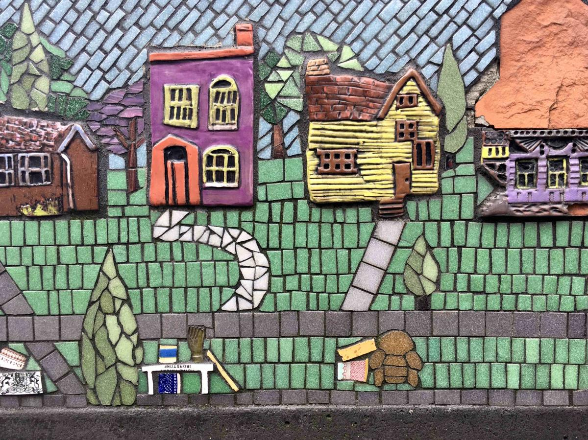 Closeup of a multi-colored mosaic showing houses and a street that's a public art work in Covington, Ky.