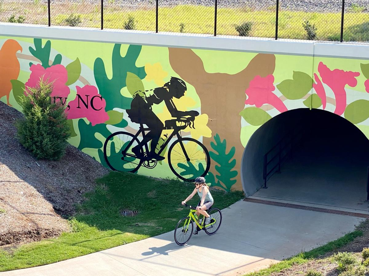 Cyclist comes out of tunnel in front of bicycle mural on Cary greenway
