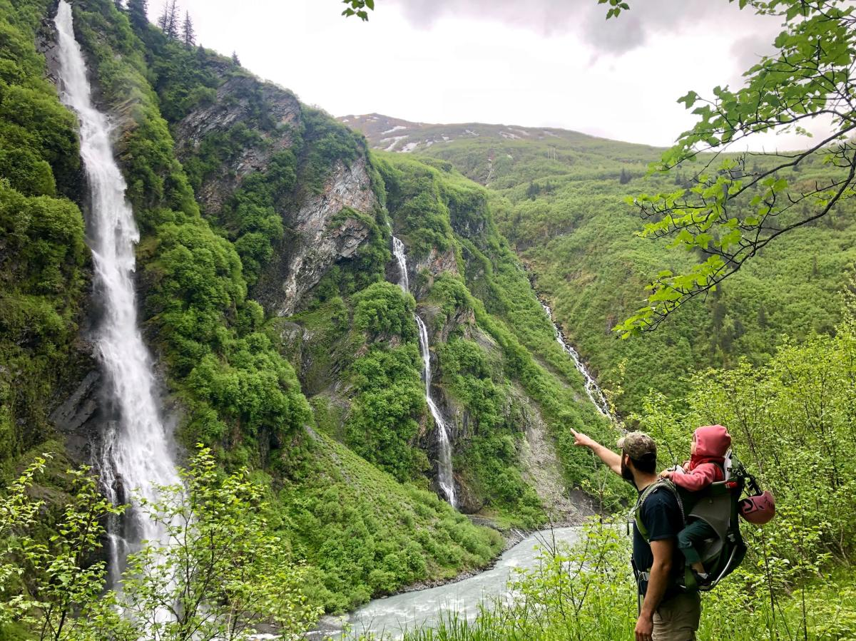a man with a baby on his back points to three waterfalls in a lush canyon