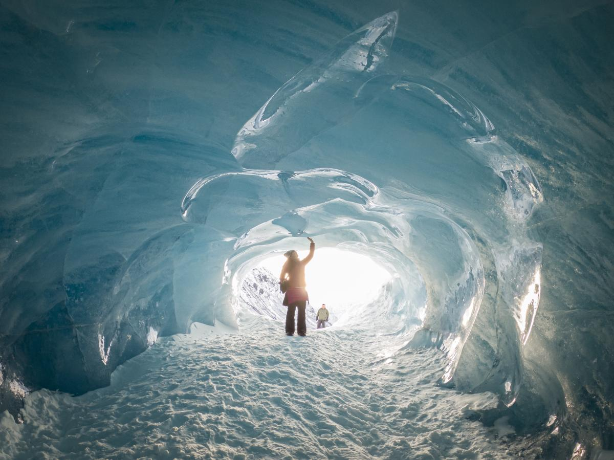 a person stands in an ice cave touching the icy walls