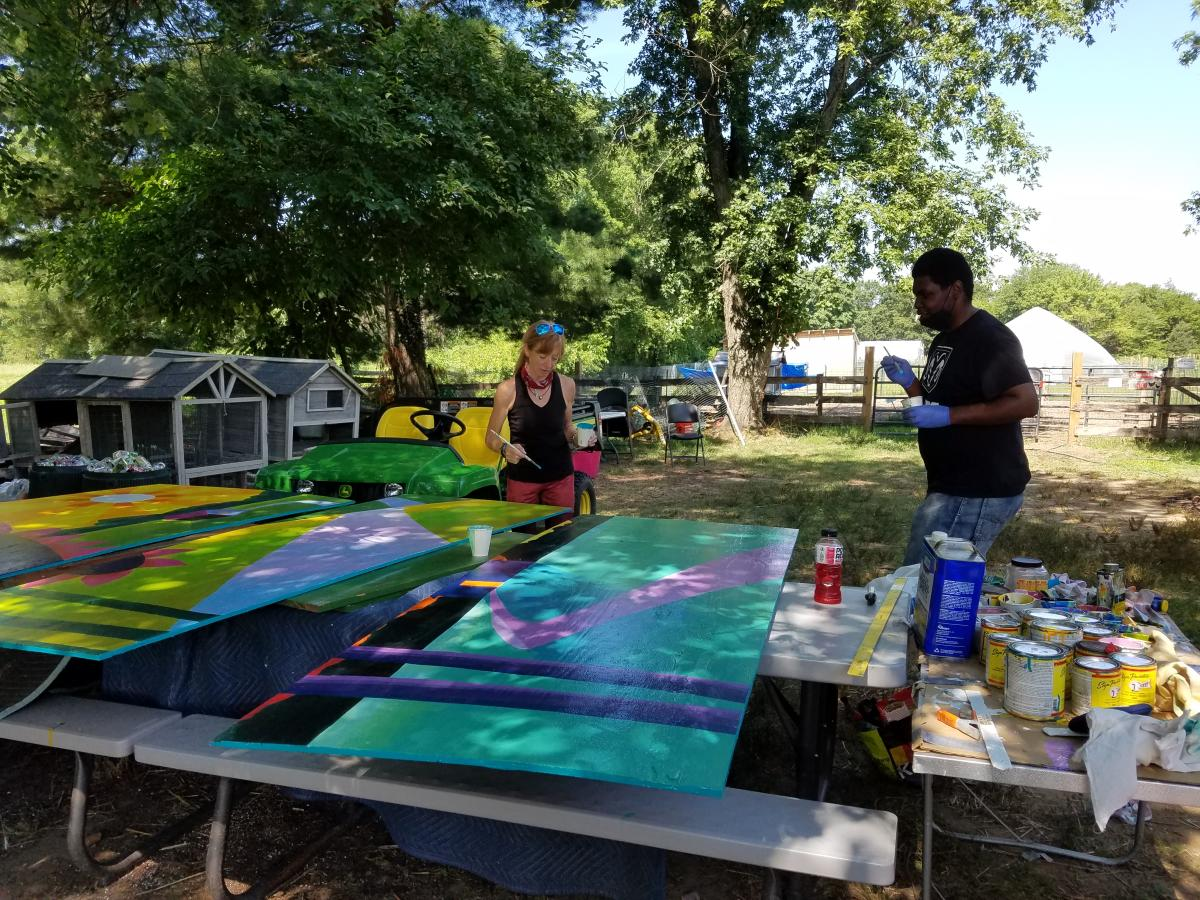 Farmhand Ron McCrary helps Cindy paint